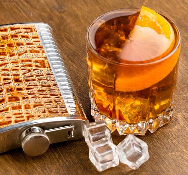 Vista superior do whisky com gelo com laranja e frasco