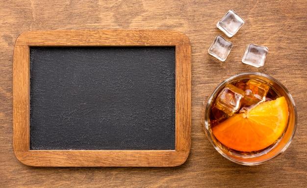 Vista superior do whisky com laranja e lousa em branco