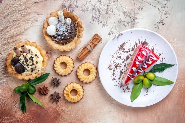 Vista superior doces cupcakes biscoitos frutas cítricas canela um bolo com chocolate