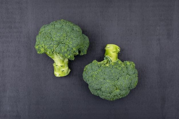 Vista superior dois cachos de brócolis na superfície preta