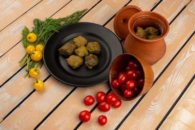 Vista superior dolma famosa carne picada oriental dentro de chapa preta, juntamente com tomate vermelho e amarelo no chão de madeira