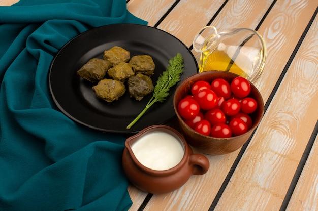 Vista superior dolma, juntamente com iogurte azeite e tomate vermelho no chão de madeira