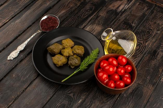 Vista superior dolma refeição de carne verde dentro de chapa preta, juntamente com o azeite de oliva e tomate cereja vermelho no marrom de madeira
