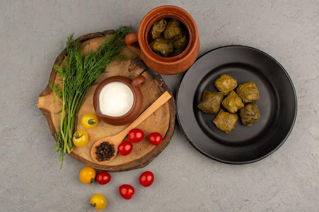 Vista superior dolma verde famosa refeição oriental juntamente com iogurte tomate no cinza