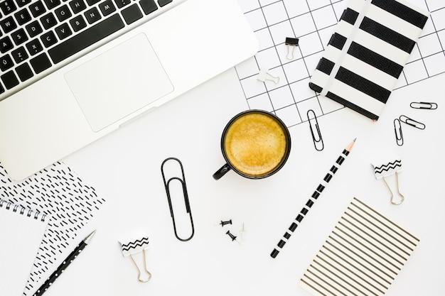 Vista superior dos artigos de papelaria de escritório com laptop e café