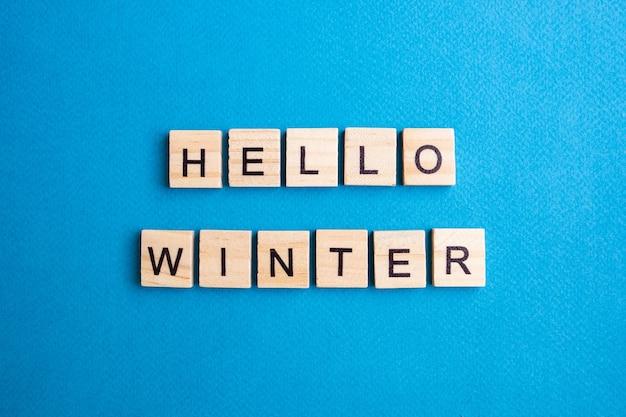 Vista superior dos blocos do alfabeto com letras em um fundo azul. olá inverno - letras.