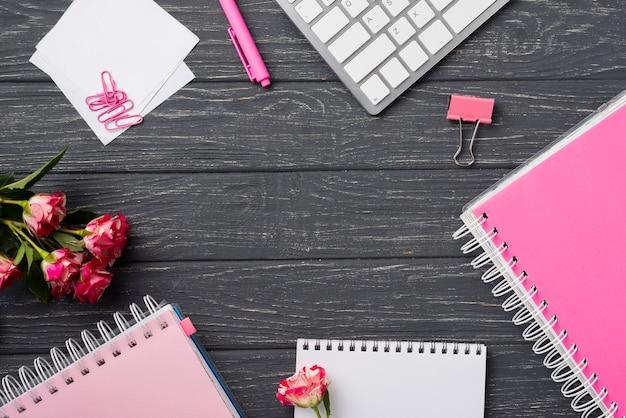 Vista superior dos cadernos na mesa de madeira com buquê de rosas e clipes de papel