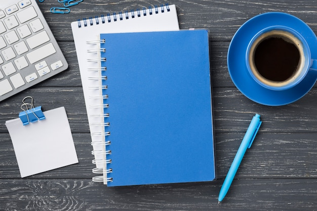 Vista superior dos cadernos na mesa de madeira e xícara de café