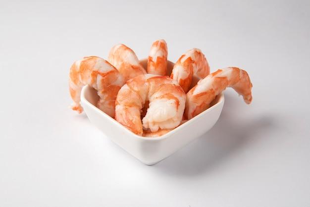 Vista superior dos camarões em um prato isolado na superfície branca