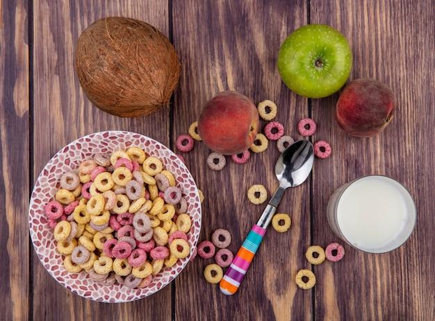 Vista superior dos cereais em uma tigela com uma colher com frutas frescas, como maçã, pêssego e um copo de leite na madeira