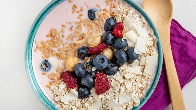 Vista superior dos cereais matinais em uma tigela com frutas e colher