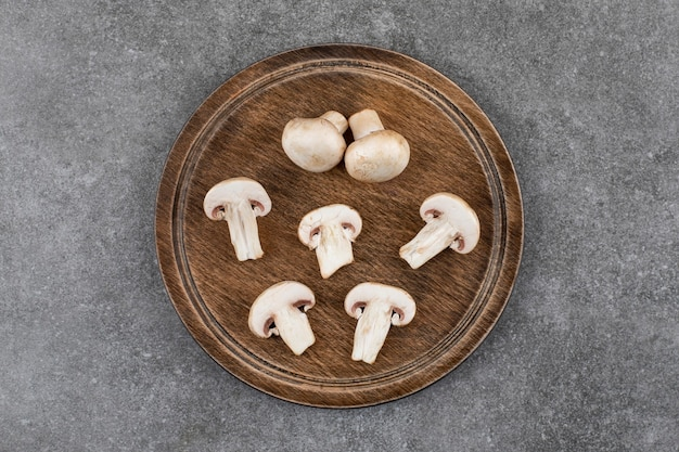 Vista superior dos cogumelos champignon. cortado ou inteiro na placa de madeira