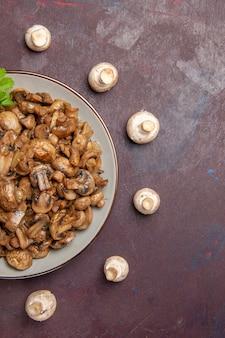 Vista superior dos cogumelos cozidos saborosos com verduras no escuro