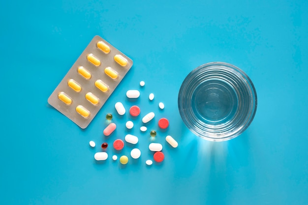 Vista superior dos comprimidos em forma de triângulo e papel alumínio com copo de água