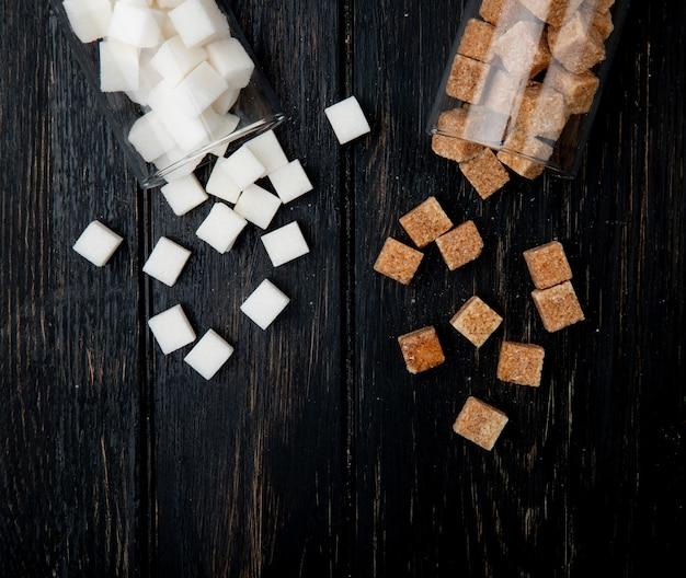 Vista superior dos cubos de açúcar branco e marrom espalhados de frascos de vidro no fundo escuro de madeira