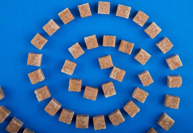 Vista superior dos cubos de açúcar mascavo, dispostos em fundo azul