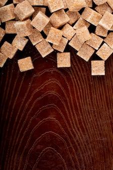 Vista superior dos cubos de açúcar mascavo espalhados sobre fundo de madeira com espaço de cópia