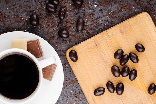 Vista superior dos doces de chocolate porca de vidro espalhados sobre uma tábua de madeira e uma xícara de café sobre fundo preto