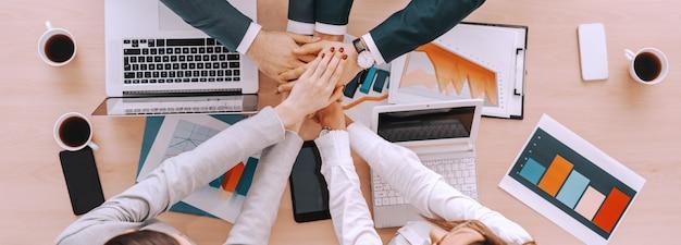 Vista superior dos empresários que empilham as mãos acima da tabela.