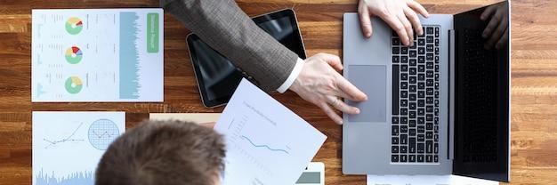 Vista superior dos empresários trabalhando em novo projeto. papéis importantes do laptop moderno com diagramas no tablet e calculadora na mesa de madeira. contador e conceito do negócio