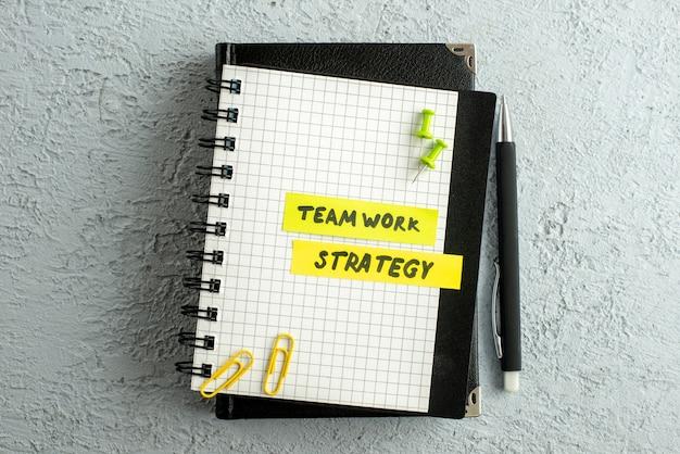 Vista superior dos escritos de estratégia de trabalho em equipe em folhas coloridas em um caderno espiral e um livro em fundo de areia cinza