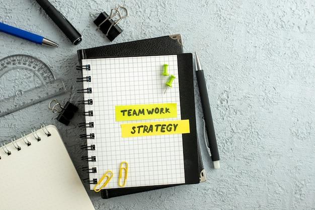 Vista superior dos escritos de estratégia de trabalho em equipe em folhas coloridas no caderno espiral e na régua do livro no fundo de areia cinza