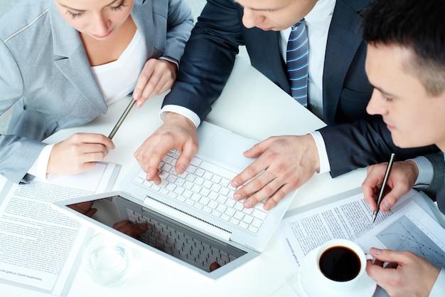 Vista superior dos executivos com portátil e chávena de café