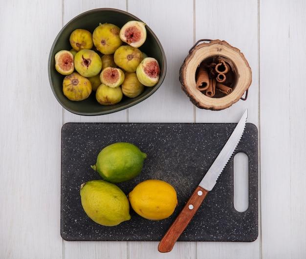 Vista superior dos figos em uma tigela com canela e limão na tábua com faca no fundo branco