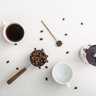 Vista superior dos grãos de café em uma xícara com chaleira e colher