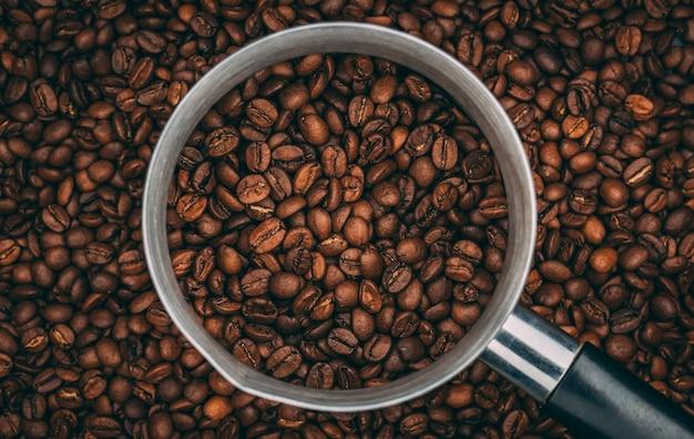 Vista superior dos grãos de café torrados em uma xícara de aço