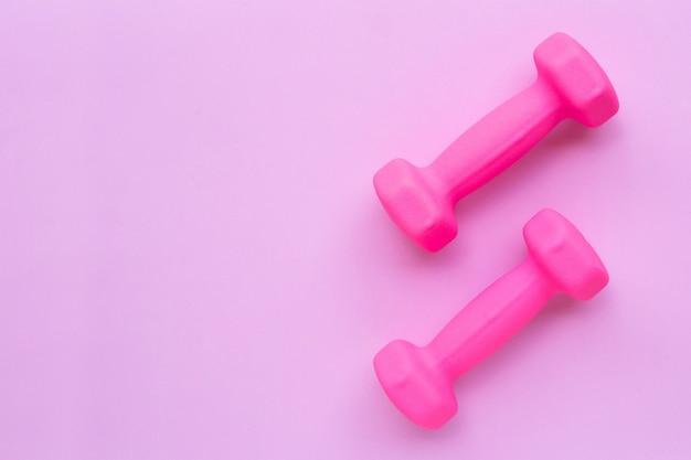 Vista superior dos halteres rosa isolados no fundo rosa.