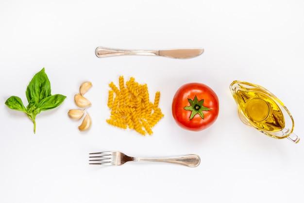 Vista superior dos ingredientes da massa e talheres em branco