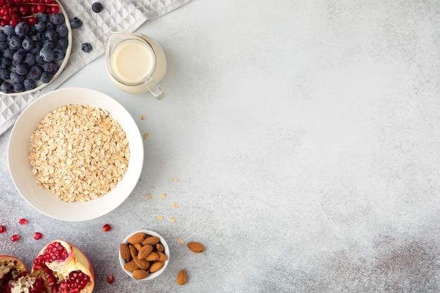 Vista superior dos ingredientes para um café da manhã saudável - aveia, nozes, mirtilos, frutas, leite ou iogurte. postura plana de comida natural da estação orgânica. postura plana, luz de fundo