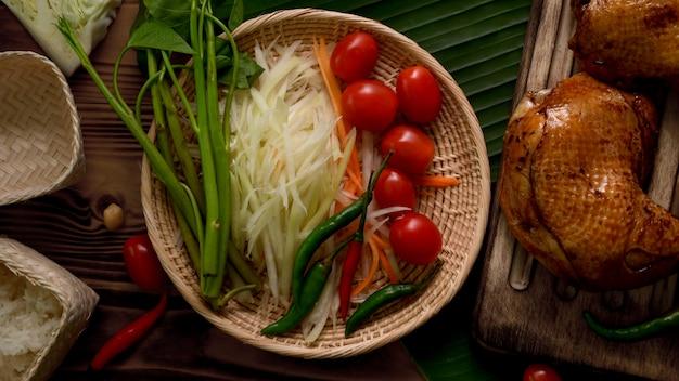 Vista superior dos ingredientes somtum, comida tradicional tailandesa com frango grelhado na bandeja de madeira
