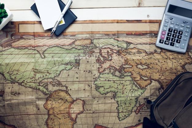 Vista superior dos itens de viagem essenciais. o cartão da caderneta do bloco da calculadora no fundo de madeira.