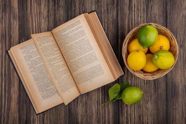 Vista superior dos limões com limas na cesta com o livro aberto sobre fundo de madeira