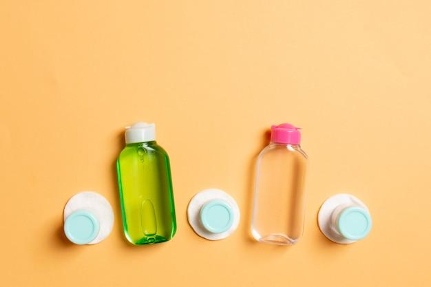Vista superior dos meios para cuidados com o rosto: frascos e potes de tônica, água de limpeza micelar, creme, almofadas de algodão sobre fundo colorido.