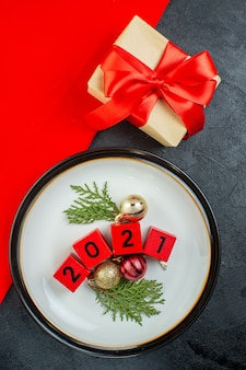 Vista superior dos números dos acessórios de decoração em um prato e um presente em uma mesa escura