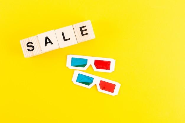 Vista superior dos óculos 3d e cubos com letras de venda isoladas em amarelo