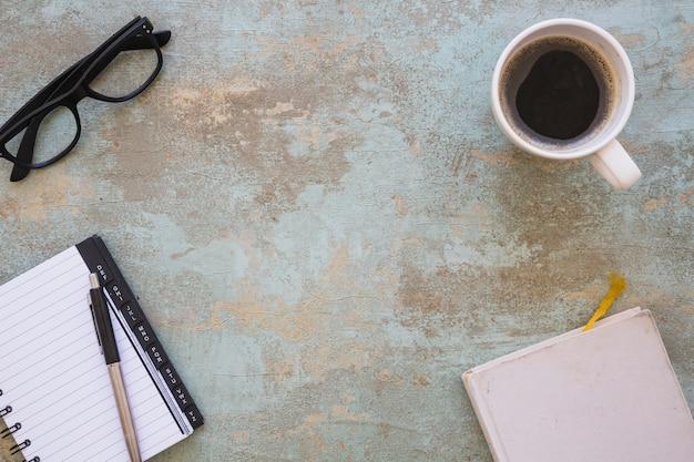 Vista superior dos óculos; bloco de notas em espiral; caneta e diário em um velho fundo rústico