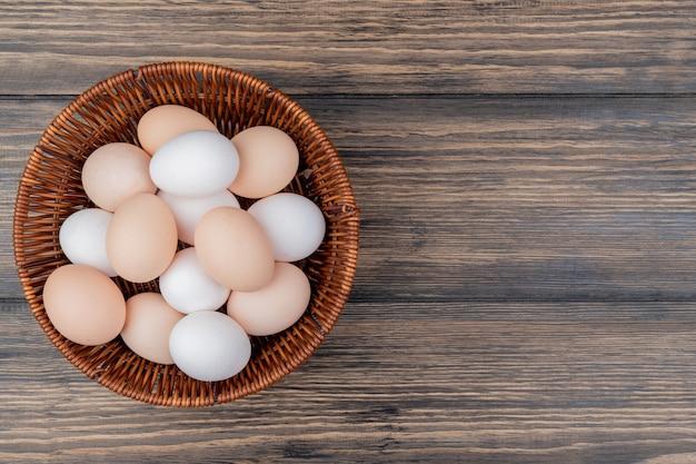 Vista superior dos ovos brancos e bege em um balde em um fundo de madeira com espaço de cópia