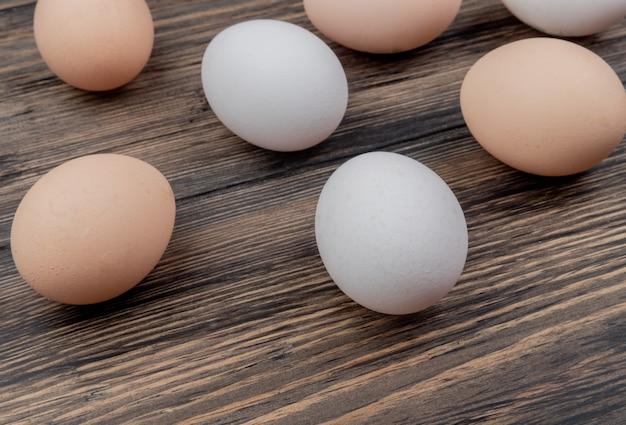 Vista superior dos ovos coloridos brancos e creme em um fundo de madeira