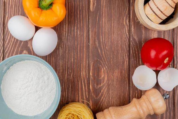 Vista superior dos ovos de galinha branca com farinha em uma tigela azul com cascas de ovos com um tomate em um fundo de madeira com espaço de cópia