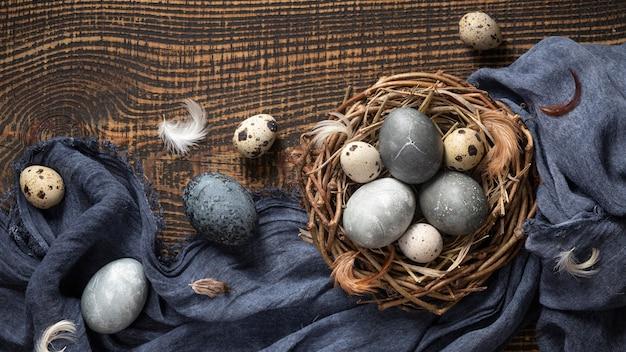 Vista superior dos ovos para a páscoa com penas no ninho de pássaro