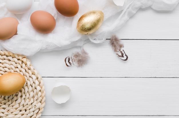 Vista superior dos ovos para a páscoa com tinta dourada e penas