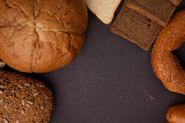 Vista superior dos pães como bagel de pão de sanduíche de espiga e centeio fatiado e pães brancos sobre fundo marrom com espaço de cópia