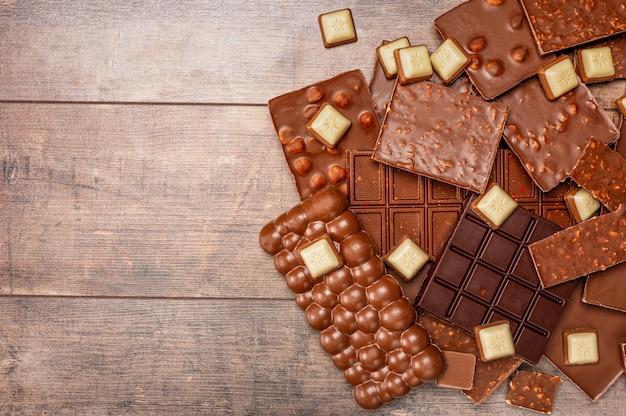 Vista superior dos pedaços de barra de chocolate com gotas de chocolate no fundo da mesa de madeira rústica. pedaços de chocolate na mesa de madeira. copie o espaço. vista do topo