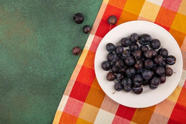 Vista superior dos pequenos abrigos de frutas azedas azuladas em um prato branco em um pano xadrez sobre um fundo verde