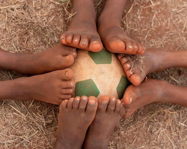 Vista superior dos pés da criança ao redor da bola de futebol