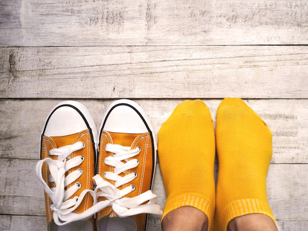Vista superior dos pés da mulher vestindo meias amarelas e tênis na madeira